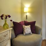 comfy chairs for small spaces with decorative cushions decorated at room corner plus standing lamp and wooden drawers plus wooden flooring