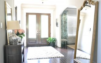 comfy entry way rugs in front of glass wood door and solid hardwood floor combined with wooden sideboard with pretty table lamp and flower vase and large mirror
