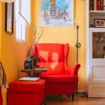 comfy orange chairs for small spaces with round wooden table and ottoman plus mirror and standing lamp plus painting on wall and wooden floor