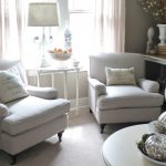 comfy white chairs for small spaces in living room with wooden coffee table and end table with pretty table lamps and fruit basket and vase