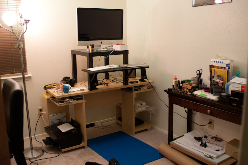 complicated modern standing desk design with black computer seating and keyboard seating with wooden storage upon blue rug aside wooden desk