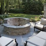 concrete patio design with in ground fire pit with gray sofa design with grassy meadow and potted plants