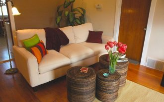 corner furniture in white color with colorful pillows and three tree trunk coffee tables small rug