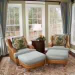 couple sunroom idea with rattan reclining sofa with blue bolster and floral patterned cushion and patterned area rug and gray curtain and glass windows