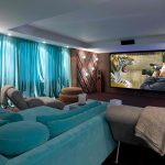 cozy home theater with large blue daybed with blue pillows light brown sofas wall lighting fixtures large flat screen