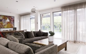 curtain inverted pleat drapes with sheer linen plus metal wall lamp in living room with gray comfy sofa and square wooden table