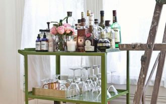 cute green metal bar carts ikea with liqours and rose flower vases and wine and cocktail glasses on wooden laminating flloor with windows plus white curtains