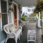 dark grey wood planks floors for porch a pair of white chairs a larger white chair with cozy seat and pillow a small square table vertical wood rail systems in white color beautiful hang plants