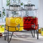dounle glass beverage dispenser with metal spigot for fresh drinks plus metal dispenser stand and lemonade glasses on wooden table