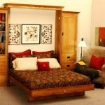 elegant furnished wooden fold up wall bed design with brown patterned bed sheet and white red pillows and evening hue chair and woden storage and artistic decoration