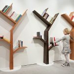 favorable triple tree shaped bookshelves design from wooden material in beige and black colors beneath white wall upon white floor