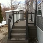 front porch for mdoern ranch home in dark grey paint color vertical metal and wood railings