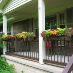 front porch with wood dark stained railings and concrete pillar attached planters for decorative plants  a pair of red chairs and a small round side table for porch a rail system for outdoor stairs