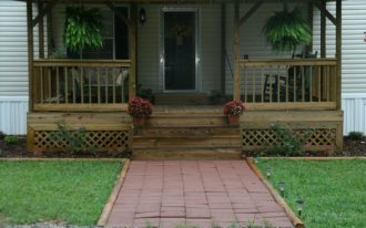 front porch with wood vertical railing and wood outdoor stairs two hanging decorative pots with plants a pair of wood rocking chairs a sofa as porch furniture