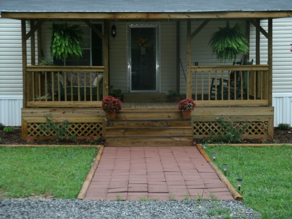 Front Porch With Wood Vertical Railing And Wood Outdoor Stairs Two Hanging  Decorative Pots With Plants