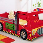 funny red fire truck race car beds for toddlers with cream bedding sheet and red pillow plus doll and colorful rug on white floor