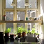 garden windows for kitchens with green plant pots above the sink plus wall mounted and pendant lighting