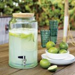 glass beverage dispenser with metal spigot and wooden lid plus blue glasses and a bowl of limes on wooden table