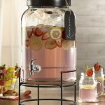 glass beverage dispenser with metal spigot with metal dispenser stand and jar glass plus a basket of fresh fruits