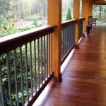 glossy and shiny wood planks porch floors plan with vertical metal railngs log pillars and a rocking chair