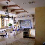 gorgeous kitchen design with white kitchen island beneath black vintage chandelier and arched glass window and blue tile spanish backsplash
