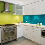 gorgeous modern kitchen design with colorful pattern of light green and blue acrylic backsplash with white cabinetry and modern kitchen set