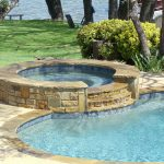 gorgeous round concrete built in hot tub design with pool aside with concrete patio aside grassy meadow aside lake