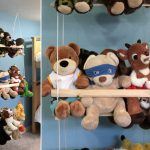gorgeous swinging model hanging stuffed animal design with wooden rack and white traditional rope beneath blue wall with various animal dolls