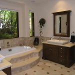 gorgeous tropical bathroom design with large glass window and recessed tub design aside wooden vanity with framed wall mirror and patterned cream tile flooring