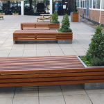 Gorgeous Wooden Furnished Bench Design With Corner Concrete Planter Boxes Design With Small Pine Tree Upon Tile Patio
