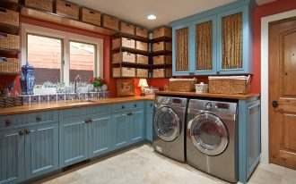 green tosca cabinet design in laundry room with washer and dryer beneath transparent storage idea with rattan baskets with glass window