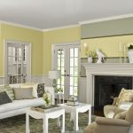 half ways light yellow color paint with chair rail molding built in craftsman fireplace mantel  a white sofa with pillows a pair of grey chairs two units of white coffee tables