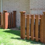 hidden pump pool equipment enclosures behind solid wooden fence at the back yard in brick wall house