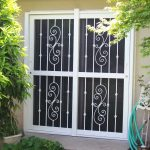 hinged screen door with two panels and  metal guard on the surface