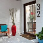 home address number with cool art deco house numbers on white wall plus glass entry door plus mat and wooden chairs plus red vase