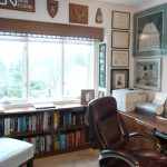 home office ideas with under window bookcase and sectional wooden desk plus brown leather swivel chair and stool plus pictures on wall  decoration