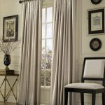 ivory inverted pleat drapes curtain on glass window plus stylish side table and comfy chair plus rug on wooden flooring