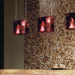 kitchen bar design with mosaic luxurious casa antical tile in golden shiny look with glamor red glossy pendants above the table
