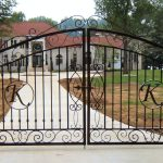 large and luxurious wrought iron main gate with letter initial