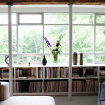 large glass window area in living room with under window bookcase with many book arrangemend and pillar plus comfy sofa with cushions