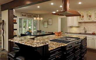 large kitchen islands with seating and storage plus marble countertop and gas stove and comfy black stool plus wooden floor and white kitchen cabinets