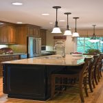 large kitchen islands with seating and storage with granite countertop plus three pendant lighting and wooden floor and sink plus wooden kitchen cabinets
