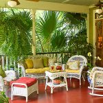 larger porch in Key West style with white rattan chairs pillows sette furniture a pair of ceiling fans wall mount rack for putting table lamp and some decorative items a lot of green and fresh plants