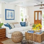 living room design inspired from Key West style with white sofa natural tree stump coffee table a rattan ball chair a pile of natural tree stump pieces as the side table a ceiling fan beautiful pillows