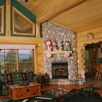log home's interior style with built in fireplace plus its natural stone construction dark green tone color sofas classic green rug for clear and shiny wood finished floors glass windows with blinds