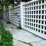long and firm white lattice fence design with concrete patio design with greenery beneath shady tree