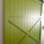 lovable and fresh green wooden barn door design with cross accent with deck style and black metal sliding rod on white wall