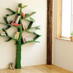 lovable green tree shaped bookshelves design beneath white wall upon wooden laminated floor aside glass window with rustic wooden pole