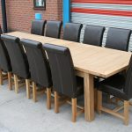 luxurious and classy black leather chairs design with long rectangle wooden natural table in outdoor concrete patio