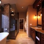 luxurious golden bathroom idea with large wooden vanity design with pendants and luxurious white tub beneath glass window aside walk in shower